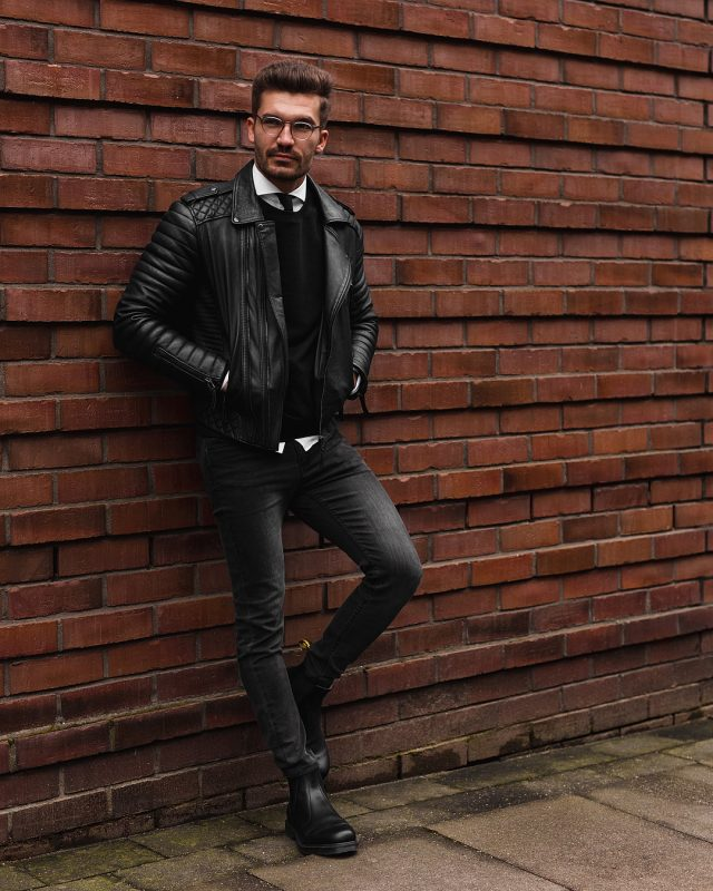 Black leather jacket, black sweater, white shirt, skinny tie, black jeans, and leather boots
