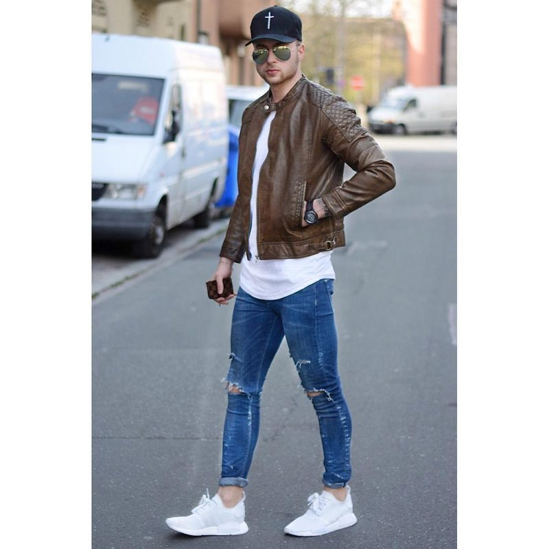 Brown leather racer jacket, white tee, blue ripped jeans, baseball cap, and white sneaker