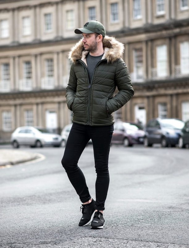 Hooded fur olive green puffer jacket, gray tee, black jeans, sneakers - puffer jacket style for guys