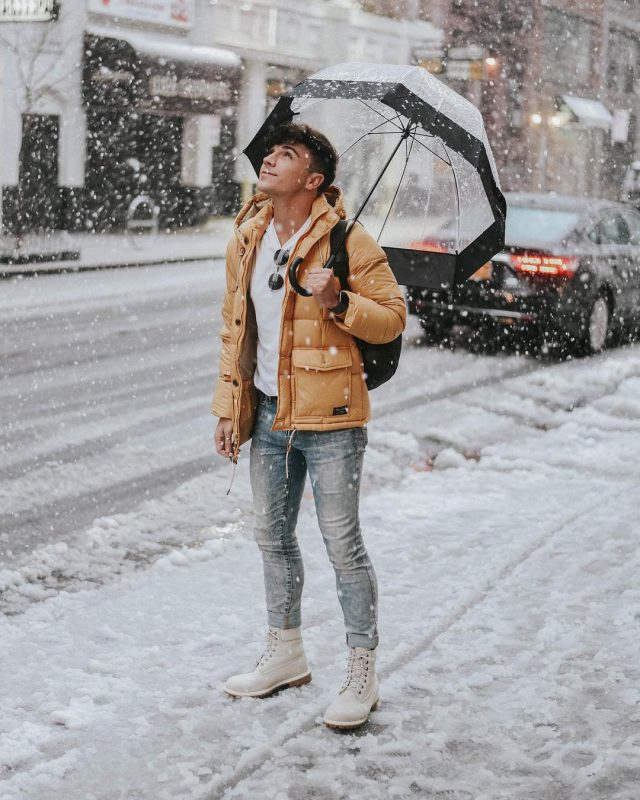 40 mens winter work outfit styles with winter boots. Light grey jungle boots, orange puffer jacket, white t-shirt, jeans 1