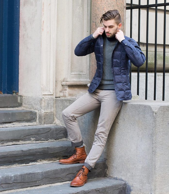 40 mens winter work outfit styles with winter boots. Brown leather brogue dress boots, blue puffer jacket, grey sweater 1